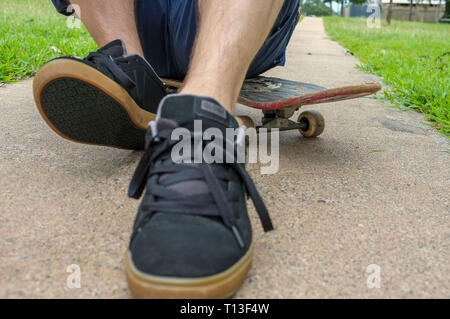 Closeup of a person sitting on a skateboard. - Stock Image