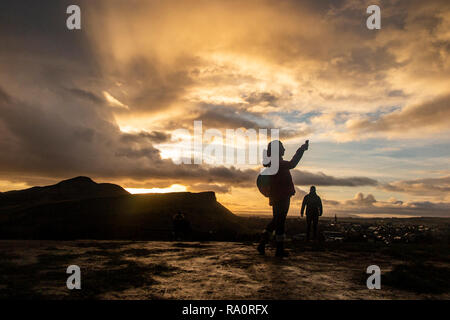 A girl tajes a selfie with Arthur's Seat in the background under a dramatic sky at dawn - Stock Image