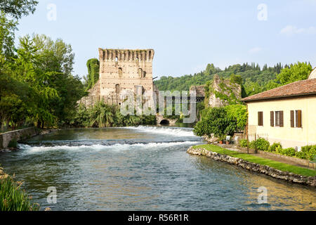 Visconti bridge of Valeggio sul Mincio at Borghetto with reflections in Mincio river, Italy . - Stock Image