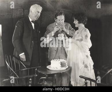 Three people enjoying a slice of cake - Stock Image