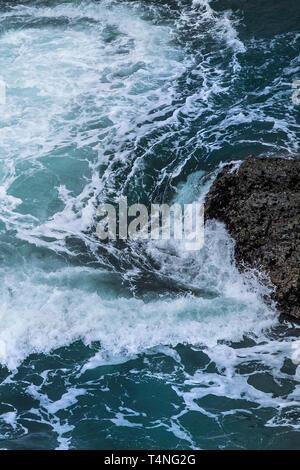Sea swirling around rocks on the coast of Cornwall, UK. - Stock Image