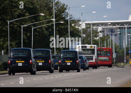 Taxi cabs and buses on Southern Perimeter Road near Heathrow Airport, London UK. - Stock Image