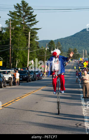 A happy clown dressed up in red, white and blue riding a unicycle in the 4th of July parade held on June 30, 2018 in Speculator, NY USA - Stock Image