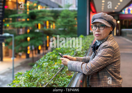 Fashionable Taiwanese woman of Chinese ethnicity out  on town looking up from mobile phone - Stock Image