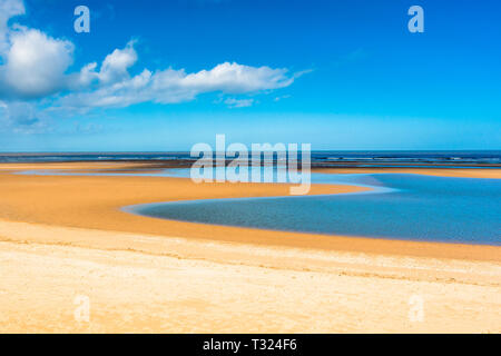 Tide pool of water at low tide on Barnham Overy Staithe beach on Holkham bay, North Norfolk coast, East Anglia, England, UK. - Stock Image