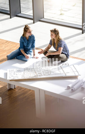 Colleagues brainstorming over architectural model - Stock Image