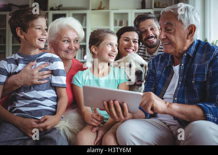 Happy multi-generation family using digital tablet in living room - Stock Image