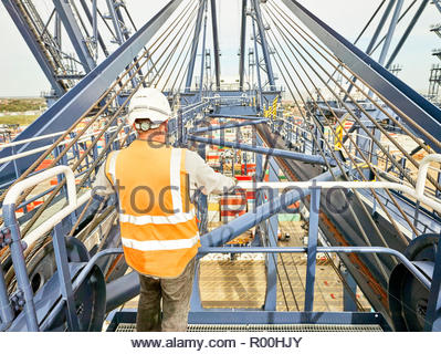 Dock worker by railing of crane - Stock Image