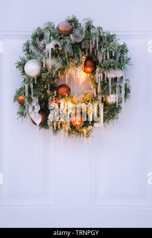 Close-up of a ice covered Christmas wreath hung on a door in winter - Stock Image