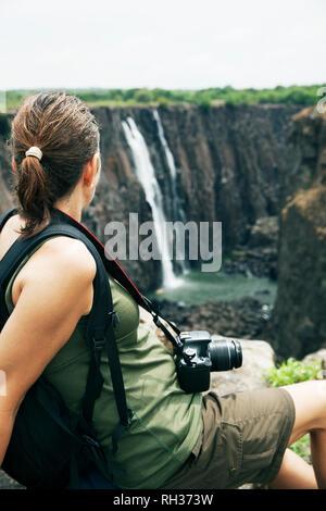 Woman looking at waterfall - Stock Image