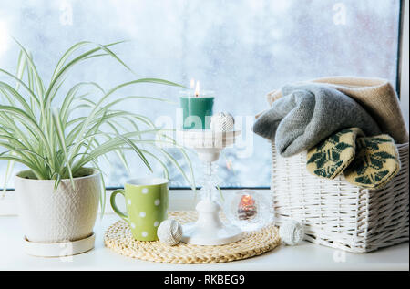 Cozy winter set on window sill. Romantic style tall candle holder, rattan basket with knitted mittens and warm plaids and blanket, snow falling outdoo - Stock Image