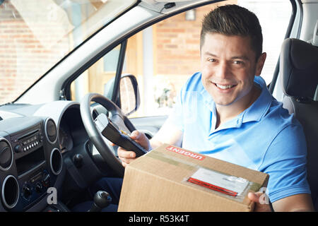 Portrait Of Courier In Van Delivering Package To House - Stock Image