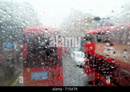 A view of double decker red buses in traffic view from top of bus interior raindrops on window on rainy day in London England UK  KATHY DEWITT - Stock Image