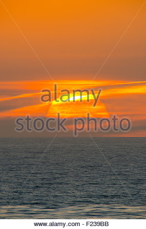 Sunset over the Pacific Ocean from La Jolla California of the huge setting sun over the sea - Stock Image