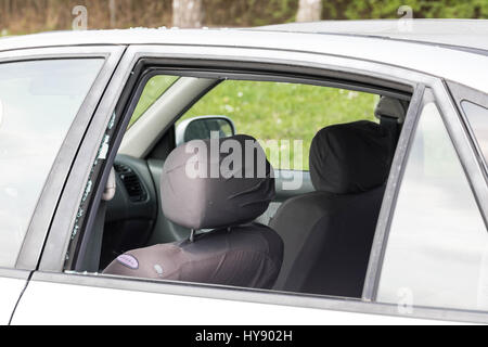 Smashed car window on a public paking space - Stock Image