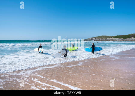 Surfers walking into the sea at surfing hotspot Fistral in Newquay in Cornwall. - Stock Image