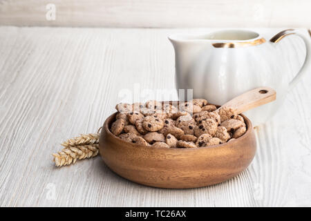 Chocolate  chip cookie cereal with milk on white wooden table - Stock Image