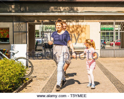Poznan, Poland - April 18, 2019: Woman and girl holding hands walking by the entrance of the old zoo on a warm spring day. - Stock Image