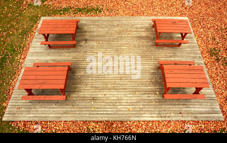 Pole aerial High Dynamic Range (HDR) image of four picnic tables on a wooden platform surrounded by autumn leaves - Stock Image