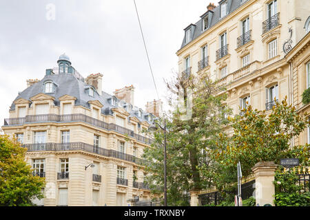 PARIS, FRANCE - JULY 22, 2017: Ancient luxury buildings facade with trees and railings with golden points in a cloudy day in Paris, France - Stock Image