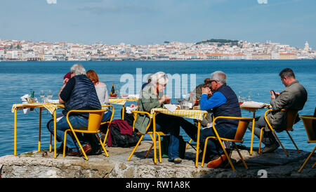Lisbon, Portugal - March 2nd, 2019: People sitting at yellow restaurant tables in the shore of the river Tagus in Cacilhas - Lisbon's cityscape in the - Stock Image