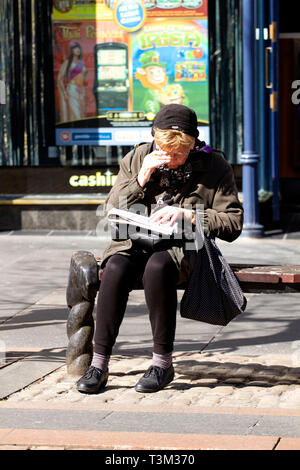 An elderly woman sitting on a city centre seat in the sunshine doing the newspaper crossword puzzle in Dundee, UK - Stock Image