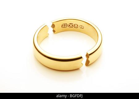 Broken Gold Wedding Ring Symbolizing Marriage Break Up - Stock Image