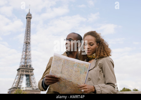 African couple looking at map - Stock Image
