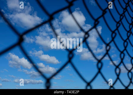 Blue sky with white clouds seen through a chainlink fence. - Stock Image