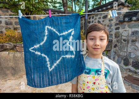 A young boy proudly poses with the scarf that he has tie dyed and is hanging outside on a washing line to dry. - Stock Image