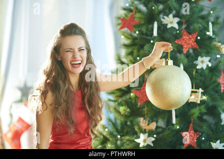 cheerful trendy woman in red dress near Christmas tree showing big gold Christmas ball - Stock Image