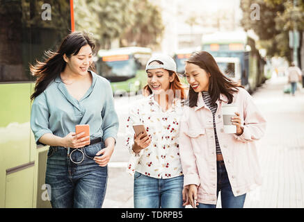 Happy Asian girls using mobile phone outdoor - Young millennial people having fun with new smartphone app technology - Stock Image
