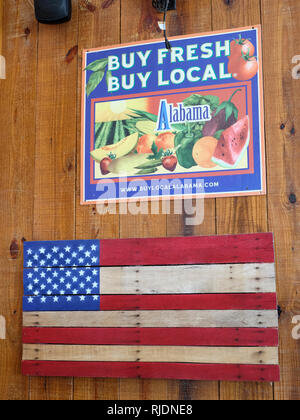 Buy Fresh Buy Local sign promoting Alabama agriculture above an American flag painted on wood in a rural Alabama farm market in Pike Road Alabama, USA - Stock Image