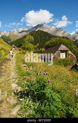 Female hiker and bordas in GR-11 footpath with Posets massif at the background in Viadós (Chistau valley, Sobrarbe, Huesca, Pyrenees, Aragon, Spain) - Stock Image