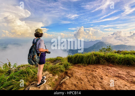 Hiker asian teens girl with camera and backpack wear caps and glasses looking beautiful landscape nature of mountain - Stock Image
