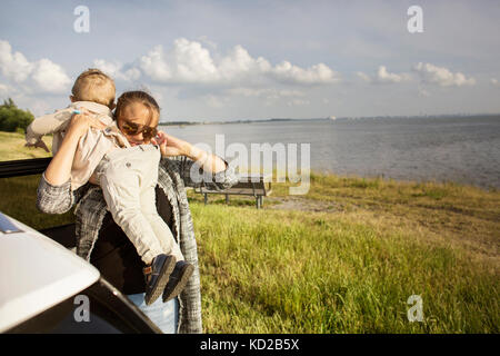 Mother holding son (18-23 months) by sea - Stock Image