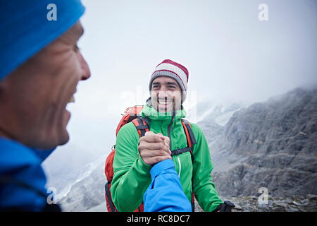Hikers congratulating themselves, Mont Cervin, Matterhorn, Valais, Switzerland - Stock Image