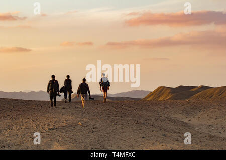 Four photographer trek the horizon of the wadi el gamal desert, Egypt - Stock Image