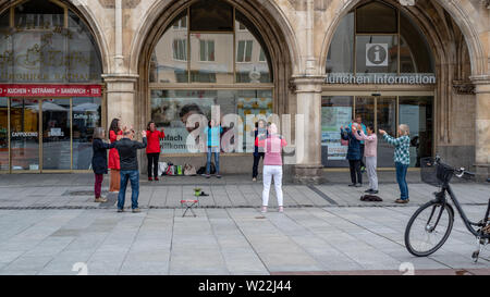 Munich, Bavaria, Germany - May 28, 2019. Group of unidentified people practicing tai chi in front of the tourist center, Marienplatz, in the morning- - Stock Image
