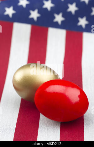 red and gold nest eggs placed on American flag in vertical photograph.  Selective focus on opposing symbols of profit and loss, success and failure, r - Stock Image