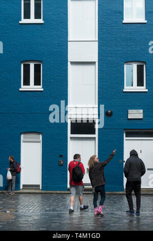 People standing in front of a building painted in blue and white in Clink Street in London. - Stock Image