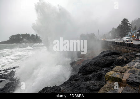 Stormy surf crashes on the rocky Pacific shoreline and seawall, washing over U.S. Route 101 and car in Depoe Bay, - Stock Image