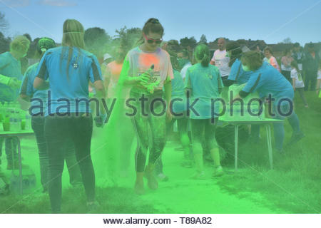Garstang, Lancashire, England, UK, 12 May 2019. Participants get covered in paint at the Garstang Colour Dash, a 5km fun run filled with colour on a glorious sunny day. The popular event raises money for St Johns Hospice, a local independent charity providing care and support for patients and families living with life shortening conditions in North Lancashire and South Lakes.   Credit Keith Douglas News/Alamy Live News - Stock Image