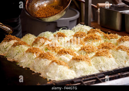 Japanese okonomi-yaki with soba noodles on top of cabbage - Stock Image