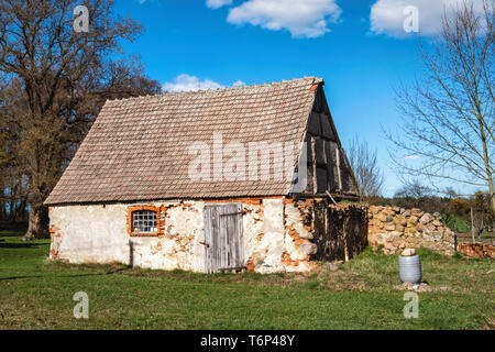 Derelict old barn building with stone exterior and half timbered tudor-style facade on Gutshaus Manor House estate, Friedenfelde,Gerswalde Brandenburg - Stock Image