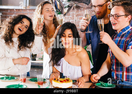 Young girl celebrates her birthday blowing out the candles with her friends - Stock Image
