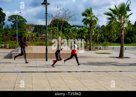 Two young African woman and a man run along a promenade in Malabo, the capital of Equatorial Guinea - Stock Image