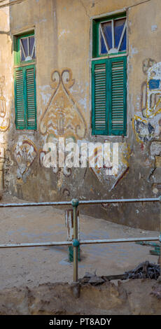 Two adjacent broken windows with closed green shutters and grunge stone wall in abandoned Darb El Labana district, Cairo, Egypt - Stock Image