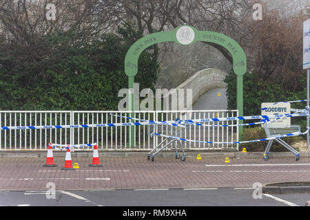 Trowbridge, Wiltshire, UK. 14th February 2019. Overnight there was a double stabbing near the Tesco Extra store. One victim rumoured to be critical. View of the Bridge into the Country park with crime scene markers leading over the bridge Credit: Starsphinx/Alamy Live News - Stock Image
