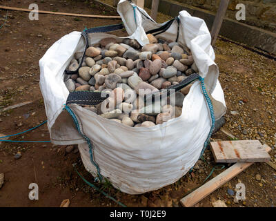 A bag of building material large smooth sea pebbles for garden use - Stock Image